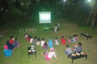 RHD. Kelas Komunitas, orang tua, dan warga nonton bersama film Le Temps d'un Échange di pelataran Mappasomba, Rumah Hijau Denassa (RHD).